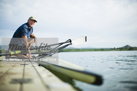 A middle-aged man on a jetty preparing a rowing boat for an outing. Stock Photo - Premium Royalty-Free, Image code: 6118-07351859