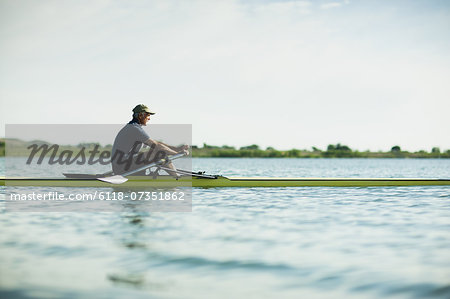 A middle-aged man in a rowing boat on the water. Stock Photo - Premium Royalty-Free, Image code: 6118-07351862
