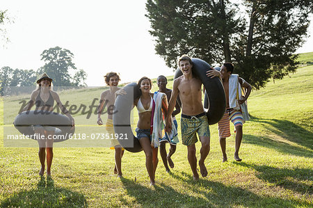 A group of young people, boys and girls, holding towels and swim floats, going for a swim. Stock Photo - Premium Royalty-Free, Image code: 6118-07351921