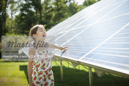 A child in the fresh open air on a sunny day, beside solar panels at a farm in New York State, USA. Stock Photo - Premium Royalty-Free, Image code: 6118-07351945