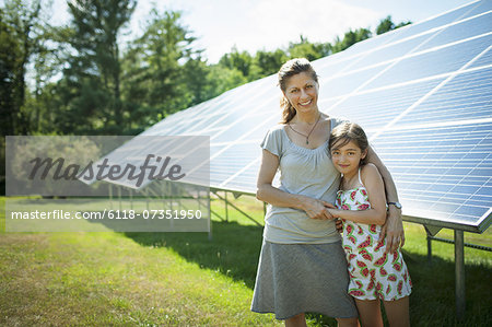 A child and her mother in the fresh open air, beside solar panels on a sunny day at a farm in New York State, USA. Stock Photo - Premium Royalty-Free, Image code: 6118-07351950