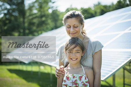 A child and her mother in the fresh open air, beside solar panels on a sunny day at a farm in New York State, USA. Stock Photo - Premium Royalty-Free, Image code: 6118-07351953