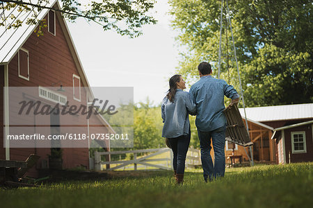 Two people, man and woman in the yard of a traditional farm in the USA. Stock Photo - Premium Royalty-Free, Image code: 6118-07352011