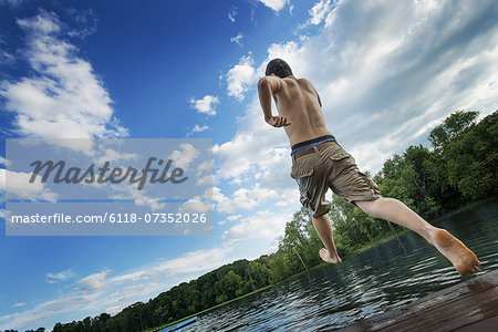 A boy taking a running jump into a calm pool of water, from a wooden jetty. Stock Photo - Premium Royalty-Free, Image code: 6118-07352026