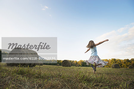 A field full of tall rounded hay bales, and a young girl dancing with her arms outstretched on the stubble field. Stock Photo - Premium Royalty-Free, Image code: 6118-07352035