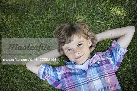 A boy lying on the grass, hands behind his head. Stock Photo - Premium Royalty-Free, Image code: 6118-07352166