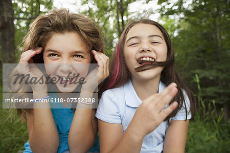 Two girls, friends sitting side by side, playing and laughing. Stock Photo - Premium Royalty-Free, Image code: 6118-07352388