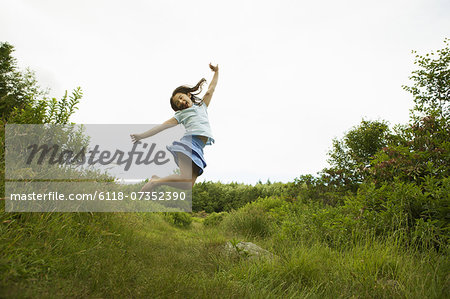 A young girl, leaping for joy, kicking up her heels in the air. Stock Photo - Premium Royalty-Free, Image code: 6118-07352390