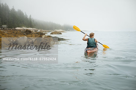 A man paddling a kayak on calm water in misty conditions. New York State, USA Stock Photo - Premium Royalty-Free, Image code: 6118-07352424