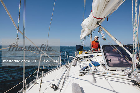 Middle aged man steering sailboat on Puget Sound, Washington, USA Stock Photo - Premium Royalty-Free, Image code: 6118-07352544