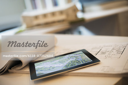 An architectural practice office. A desktop with blueprints and architectural plans, and a computer tablet. Architect's model of a house. Stock Photo - Premium Royalty-Free, Image code: 6118-07352600