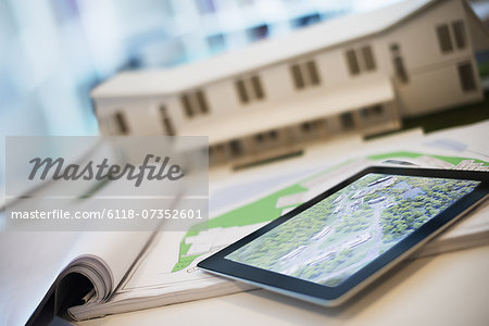An architectural practice office. A desktop with blueprints and architectural plans, and a computer tablet. Architect's model of a house. Stock Photo - Premium Royalty-Free, Image code: 6118-07352601