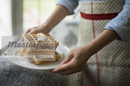 A woman holding a plate of fresh cooked waffles, with cream on top. Stock Photo - Premium Royalty-Free, Image code: 6118-07352636