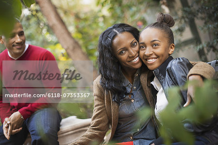 Scenes from urban life in New York City. Three people, two adults and a teenage girl. Mother and daughter hugging. Stock Photo - Premium Royalty-Free, Image code: 6118-07353367
