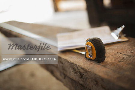 A reclaimed timber yard. Recycled plank of wood, measuring tape and a clipboard with paperwork. Stock Photo - Premium Royalty-Free, Image code: 6118-07353394