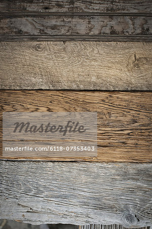 A heap of recycled reclaimed timber planks of wood. Environmentally responsible reclamation in a timber yard. Varieties of wood, with grain and colour details. Stock Photo - Premium Royalty-Free, Image code: 6118-07353403
