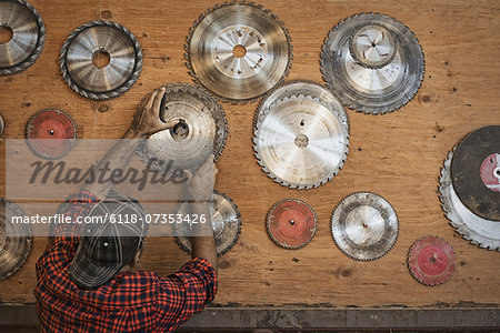 A reclaimed lumber workshop. A man reaching up to a storage board for circular saw blades to replace a blade. Stock Photo - Premium Royalty-Free, Image code: 6118-07353426