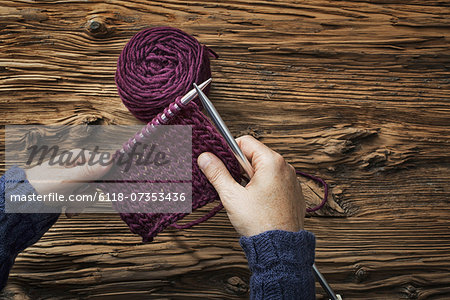 A woman holding two knitting needles, and a piece of knitting, in purple wool. Stock Photo - Premium Royalty-Free, Image code: 6118-07353436