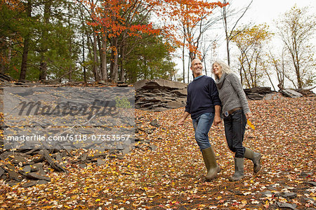 A couple, man and woman on a day out in autumn walking through fallen leaves. Holding hands.