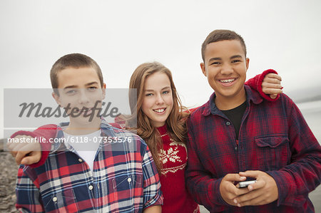 A day out at Ashokan lake. Three teenagers, boys and a girl in a row. Friends. Stock Photo - Premium Royalty-Free, Image code: 6118-07353576