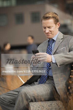 A man sitting on a bench outside a large building,  looking at a cell phone screen or mobile phone. Stock Photo - Premium Royalty-Free, Image code: 6118-07353622