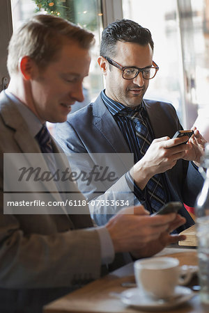 Business people in the city. Two men sitting at a cafe table checking their mobile phone messages and keeping in touch. Stock Photo - Premium Royalty-Free, Image code: 6118-07353634