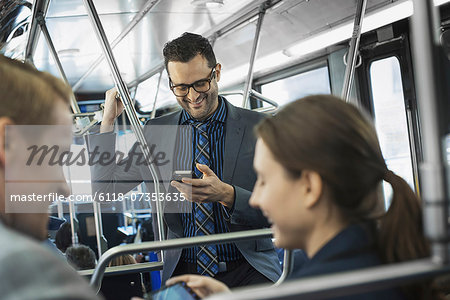 Business people in the city. Three people on the move, two men and a woman, on the bus. Stock Photo - Premium Royalty-Free, Image code: 6118-07353635