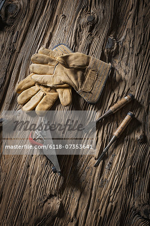 A reclaimed lumber yard workshop. A pair of leather working gloves, and handheld traditional tools. Stock Photo - Premium Royalty-Free, Image code: 6118-07353641