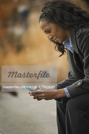 City life. A woman in a coat, checking and texting, keeping in contact, using a mobile phone. Stock Photo - Premium Royalty-Free, Image code: 6118-07353685
