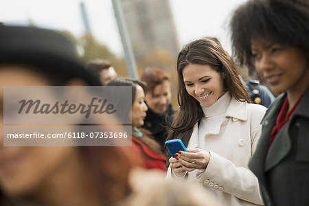 City life. A group of people on the go, keeping in contact, using mobile phones, and talking to each other. A crowd of women. Stock Photo - Premium Royalty-Free, Image code: 6118-07353696