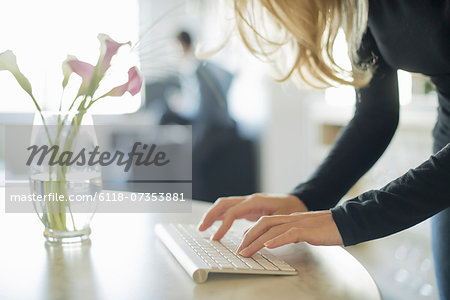 Couple relaxing at home, woman using keyboard Stock Photo - Premium Royalty-Free, Image code: 6118-07353881