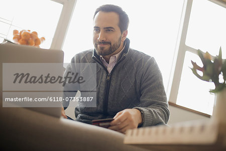 Man on-line shopping on laptop on sofa with credit card Stock Photo - Premium Royalty-Free, Image code: 6118-07353887