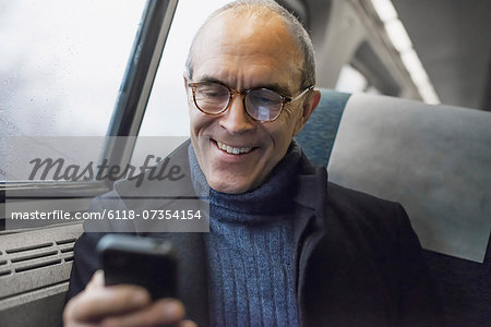 A mature man sitting by a window in a train carriage, using his mobile phone, keeping in touch on the move. Stock Photo - Premium Royalty-Free, Image code: 6118-07354154