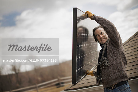 A man carrying a large solar panel across a farmyard. Stock Photo - Premium Royalty-Free, Image code: 6118-07354193