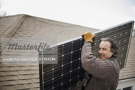 A man carrying a large solar panel across a farmyard. Stock Photo - Premium Royalty-Free, Image code: 6118-07354194