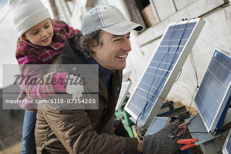 A man giving a child a piggybank while trying to connect the leads for solar power panels. Stock Photo - Premium Royalty-Free, Image code: 6118-07354205