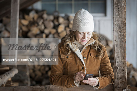 An organic farm in upstate New York, in winter. A woman in sheepskin coat and woollen hat using a cell phone. Stock Photo - Premium Royalty-Free, Image code: 6118-07354291