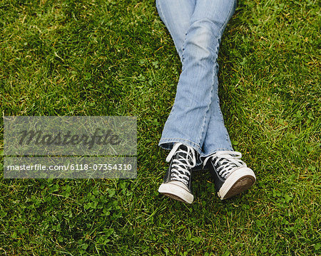 A ten year old girl lying on the grass. Cropped view of her lower legs. Wearing sneakers and faded blue jeans. Legs crossed at the ankles. Stock Photo - Premium Royalty-Free, Image code: 6118-07354310