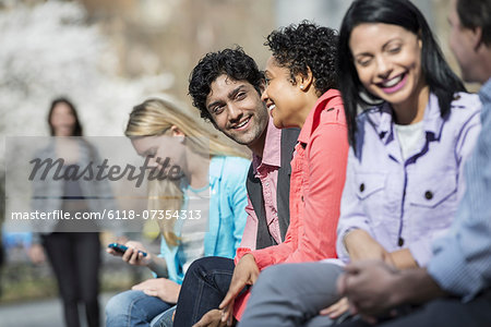 People outdoors in the city in spring time. Five people sitting in a row, one looking at a mobile phone. A woman approaching in the distance. Stock Photo - Premium Royalty-Free, Image code: 6118-07354313