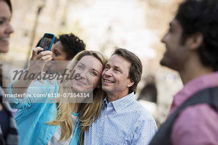 People outdoors in the city in spring time. A woman using her cell phone to take a photograph. A group of friends, men and women. Stock Photo - Premium Royalty-Free, Image code: 6118-07354314