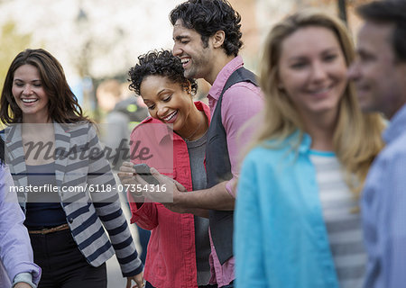 People outdoors in the city in spring time. A group of men and women, two looking at a cell phone screen and laughing. Stock Photo - Premium Royalty-Free, Image code: 6118-07354316