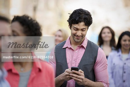 People outdoors in the city in spring time. A group of men and women. A man looking at his cell phone. Stock Photo - Premium Royalty-Free, Image code: 6118-07354318
