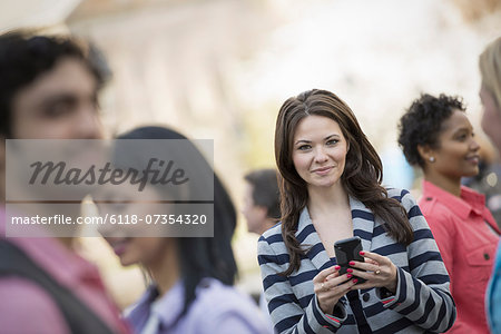 People outdoors in the city in spring time. New York City park. A young woman holding a mobile phone, and looking up at the camera. Stock Photo - Premium Royalty-Free, Image code: 6118-07354320