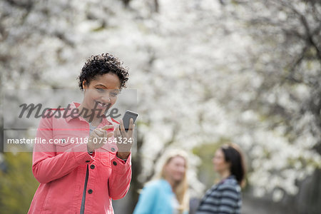 People outdoors in the city in spring time. White blossom on the trees. A young woman checking her cell phone, and laughing. Stock Photo - Premium Royalty-Free, Image code: 6118-07354324