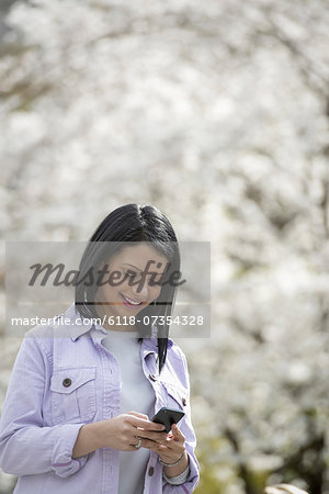 Outdoors in the city in spring time. New York City park. White blossom on the trees. A young woman checking her mobile phone and smiling. Stock Photo - Premium Royalty-Free, Image code: 6118-07354328