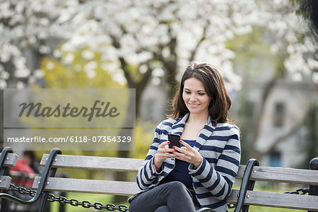 Outdoors in the city in spring time. New York City park. White blossom on the trees. A woman sitting on a bench holding her mobile phone. Stock Photo - Premium Royalty-Free, Image code: 6118-07354329
