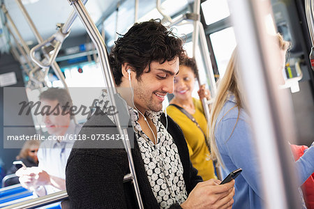 New York City park. People, men and women on a city bus. Public transport. Keeping in touch. A young man checking his cell phone. Stock Photo - Premium Royalty-Free, Image code: 6118-07354341