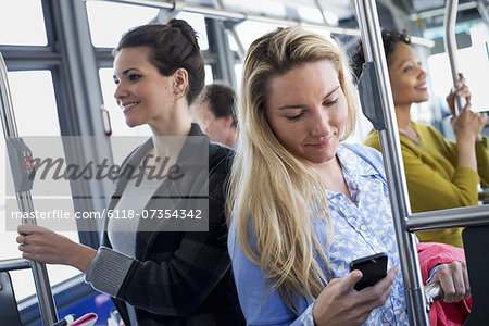 New York City park. People, men and women on a city bus. Public transport. Keeping in touch. A young woman checking or using her cell phone. Stock Photo - Premium Royalty-Free, Image code: 6118-07354342