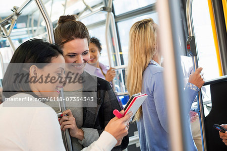 New York City park. People, men and women on a city bus. Public transport. Two women looking at a handheld digital tablet. Stock Photo - Premium Royalty-Free, Image code: 6118-07354343
