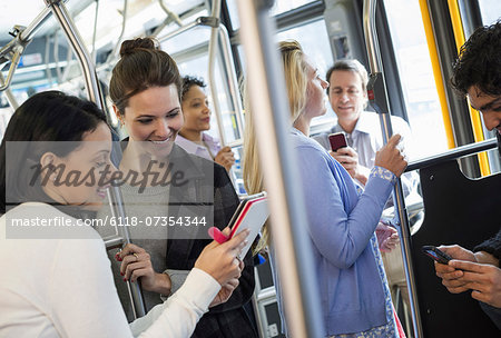 New York City park. People, men and women on a city bus. Public transport. Two women looking at a handheld digital tablet. Stock Photo - Premium Royalty-Free, Image code: 6118-07354344